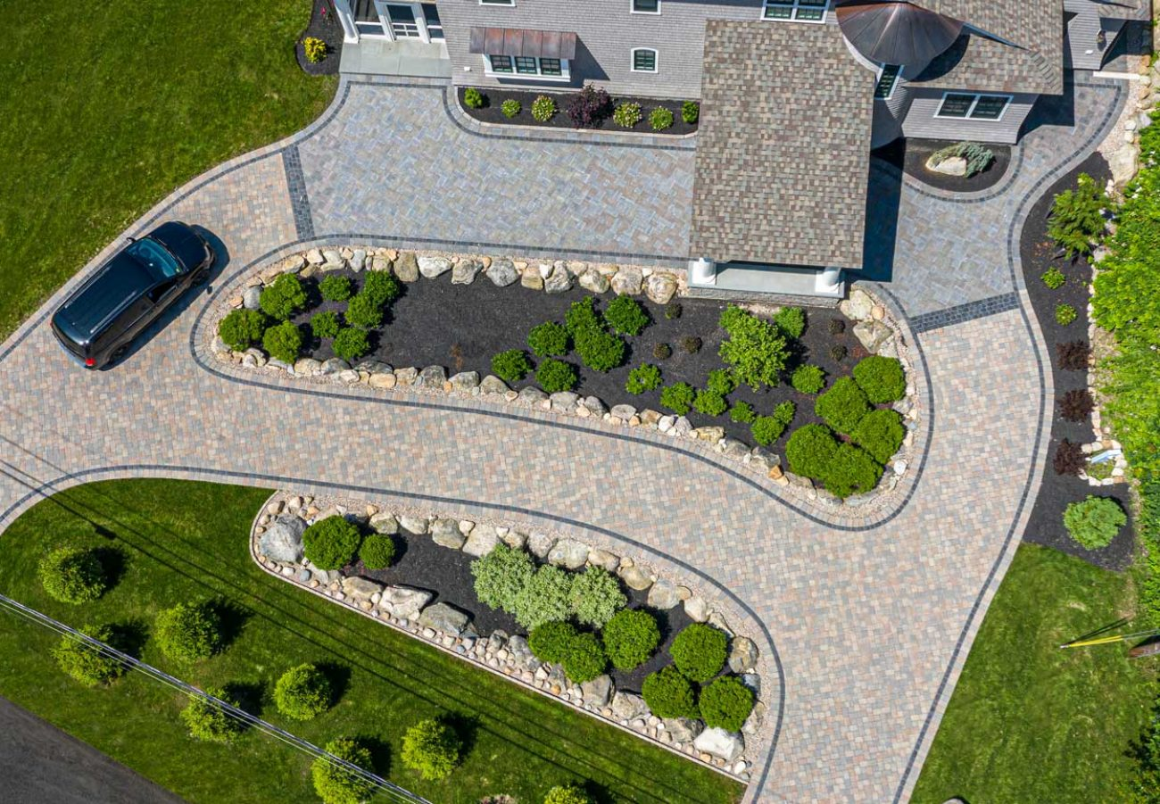 Wide arial shot of a winding Camelot driveway with a Courtstone accent with a car in the driveway